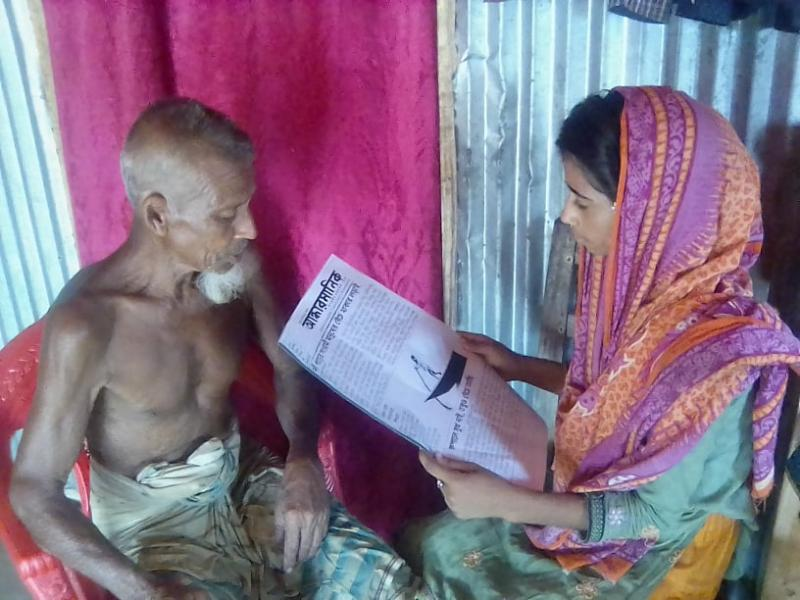 The village teenager Sonia Akter is reading the community newspaper. Senior Citizen Abdul Hamid is heartily listening to the village story.